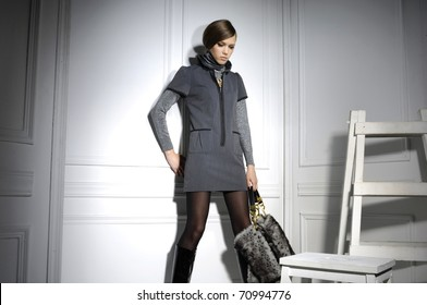High fashion model holding bag posing wooden ladder in the studio