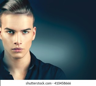 High Fashion model man portrait isolated on dark background. Handsome guy closeup. Stylish haircut, hairstyle. Hair style. Vogue style image of elegant boy