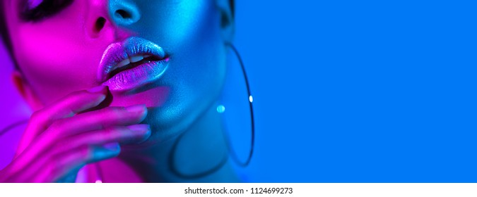 High Fashion model metallic silver lips woman in colorful bright neon blue and purple lights posing in studio, beautiful girl, trendy glowing make-up, colorful make up. Glitter Vivid neon makeup