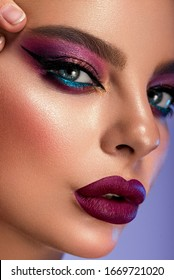 High Fashion model multicolor lips and face woman in colorful bright neon uv blue and purple lights, posing in studio, beautiful girl, glowing make-up, colorful make up. Glitter Vivid neon makeup