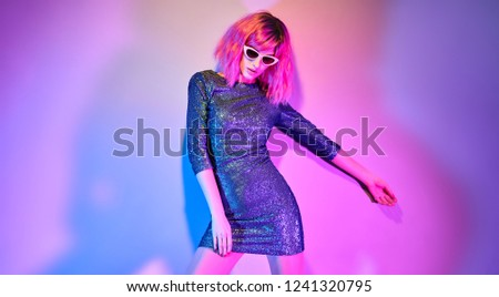 620e3a69 High Fashion Model in Trendy Sequin Dress dance in colorful bright neon  blue and purple lights