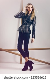 high fashion model wearing leather jacket, black trousers and black high heels posing in the studio