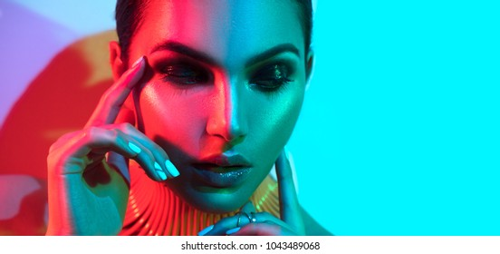 High Fashion model woman in colorful bright lights posing in studio, portrait of beautiful sexy girl with trendy make-up and manicure. Neon Art design, colorful make up. On colourful vivid background