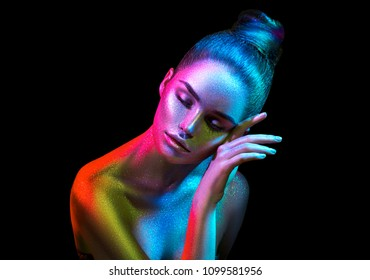 High Fashion model woman in colorful bright sparkles and neon lights posing in studio, portrait of beautiful sexy girl, trendy glowing make-up. Art design colorful make up. Glitter Vivid neon makeup
