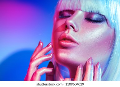 High Fashion model woman in colorful bright sparkles and neon lights posing in studio, portrait of beautiful girl, trendy glowing make-up. White hair, colorful make up. Glitter Vivid neon makeup