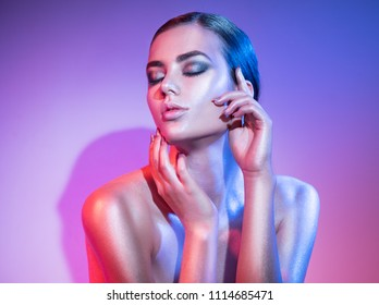 High Fashion model woman in colorful bright sparkles and neon lights posing in studio, portrait of beautiful girl, trendy glowing make-up. Art design colorful make up. Glitter Vivid neon makeup