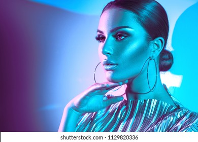 High Fashion model woman in colorful bright lights posing in studio, portrait of beautiful sexy girl with trendy make-up and earrings in bright uv light, colorful make up On colourful vivid background