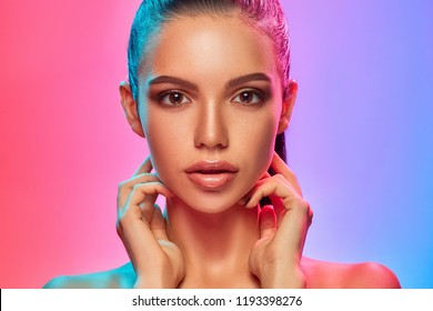 High Fashion model woman in colorful bright lights posing in studio, portrait of beautiful sexy girl with trendy make-up and manicure. Art design, colorful make up. Over colourful vivid background.