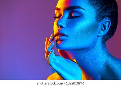 Modemodellfrau in bunten, hellen Funkeln posiert im Studio