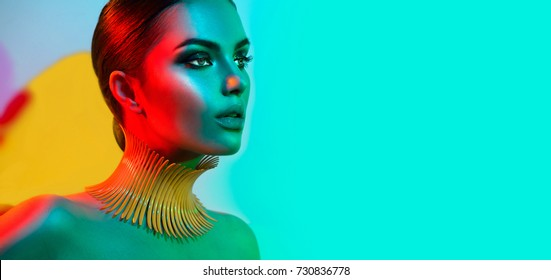 High Fashion model woman in colorful bright lights posing, portrait of beautiful sexy girl with trendy make-up. Art design, colorful make up. Over colourful vivid background. Night club dancer