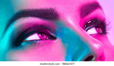 High Fashion model woman in colorful bright lights posing in studio, portrait of beautiful sexy girl with trendy eyes make-up close-up. Art design, colorful make up. Over purple vivid background.
