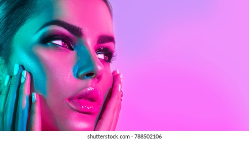 High Fashion model woman in colorful bright lights posing in studio, portrait of beautiful sexy girl with trendy make-up and manicure. Art design, colorful make up. Over colourful purple background