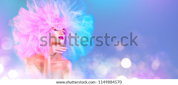 High Fashion model woman in colorful bright lights posing, portrait of beautiful sexy girl with trendy make-up and colourful pink hairdo. Art design, colorful make up. Vivid makeup. Wide angle