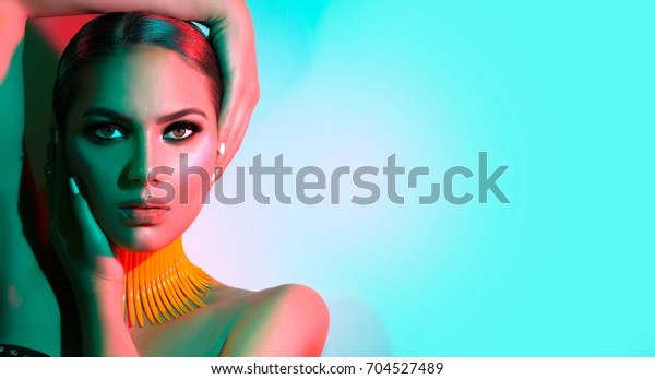 High Fashion model woman in colorful bright lights posing in studio, portrait of beautiful sexy girl with trendy make-up and manicure. Art design, colorful make up. Over colourful vivid background