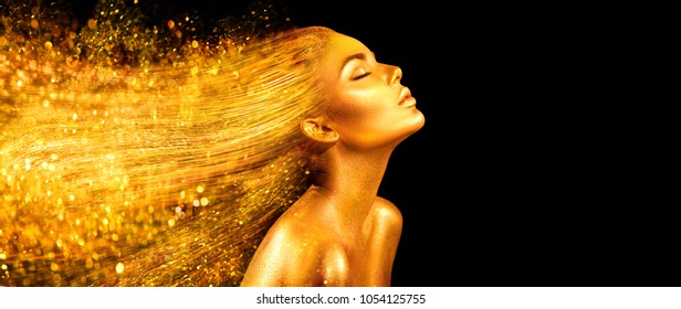 High Fashion model woman in golden bright sparkles. Art Gold skin girl face portrait closeup. Beauty gold eyes, Lips, Skin and  dyed hair. Lady with holiday Glamour shiny professional makeup on black