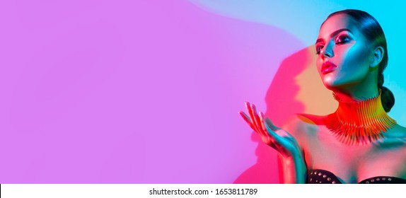 High Fashion model woman portrait in colourful bright neon lights, beautiful party girl with trendy make-up, manicure, hairstyle. Pointing hand, advertising gesture over colorful vivid background