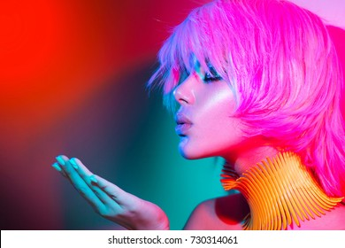 High Fashion model woman portrait in colorful bright lights, beautiful party girl with trendy make-up, manicure, haircut. Pointing hand, advertising gesture over colourful vivid background.