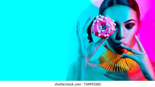 High Fashion model woman posing in studio with donut in colorful bright lights, portrait of stylish party girl with trendy make-up, haircut. Art design colorful make up. On colourful vivid background.