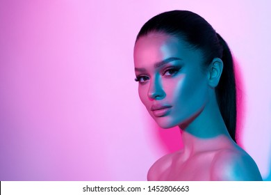 High fashion model woman's face in colorful bright neon UV blue and purple lights. Beautiful girl posing in the Studio, glowing makeup, colorful makeup. Glitter bright neon makeup.