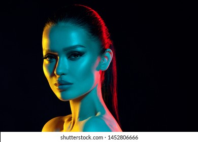 High fashion model woman's face in colorful bright neon UV blue and purple lights. Beautiful girl posing in the Studio, glowing makeup, colorful makeup. Glitter bright neon makeup. Black background