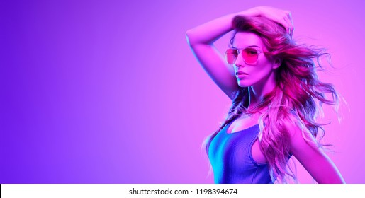 High Fashion neon light. Glamour Sexy Girl with Trendy Wavy Hairstyle, Stylish makeup. Creative Bright fashionable Portrait, Pink purple neon Color. Design Art concept, party Disco vibrations