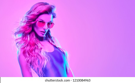 High Fashion neon light. Glamour Sexy Girl with Trendy Wavy Hairstyle, Stylish Sunglasses. Creative Bright Portrait, Pink purple Color. Design Art concept, party Disco vibrations