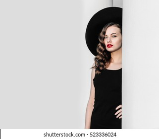 High fashion outdoor full length portrait of elegant woman in black hat and dress standing behind white pillar. Vintage-style portrait of a woman in black with red lips.