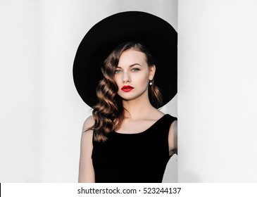 High fashion outdoor portrait of elegant woman in black hat and dress standing behind white pillar. Vintage-style portrait of a woman in black with red lips.