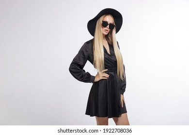 High fashion photo of a beautiful elegant young woman in a pretty black dress, hat, high heels, sunglasses, posing over white, soft gray background. Studio Shot, portrait. Blonde