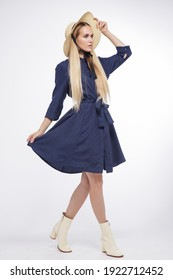 High fashion photo of a beautiful elegant young woman in a pretty blue dress, hat, boots posing over white, soft gray background. Studio Shot, portrait. Blonde