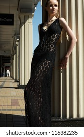 High fashion portrait of beautiful sexual woman model in black lacy dress. Outdoors trendy look. Voluptuous lady