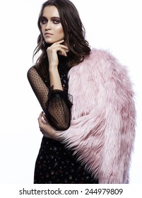 high fashion portrait of beautiful young brunette woman in black dress and pink fur coat on white background