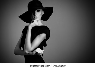 high fashion portrait of elegant woman in black and white hat and dress. Studio shot