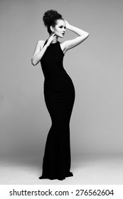 high fashion portrait of elegant woman in long black dress. Black and white studio shot