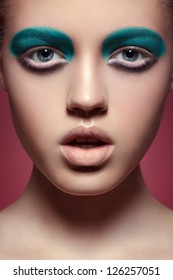 High fashion portrait of expression young woman with bright aquamarine eye make-up, pale full lips and smooth clean skin. Front beauty shoot on red background