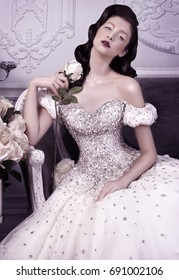 High fashion portrait of female model posing in a luxurious crystal dress. Holding a rose.
