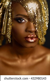 High fashion portrait of young african american female model with gold glossy makeup and hairstyle. Face art.