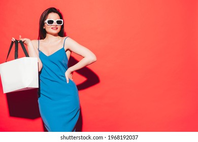 High fashion portrait of young beautiful brunette woman wearing nice blue summer dress.Sexy trendy model posing near red wall in studio.Fashionable female in sunglasses. Holding shopping bag - Shutterstock ID 1968192037