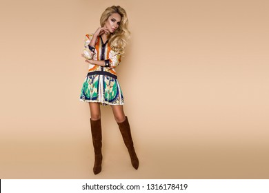 high fashion portrait of young elegant woman on beige background. Patchwork dress witch chain pattern and elegant boots. Casual, street style - Image