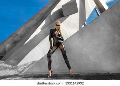 High fashion portrait of young elegant woman outdoor. Model with black sexy jumpsuit, cat eye sunglasses, grey wall background - Image