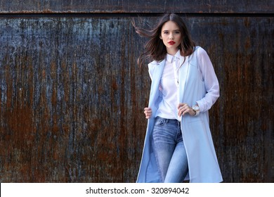 high fashion portrait of young elegant woman outdoor in blue jacket, blouse, jeans.