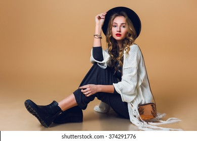 High fashion portrait of young elegant blonde  woman in black wool hat  wearing oversize white fringe  poncho with long grey dress. Studio shot. American hippie bohemian style.