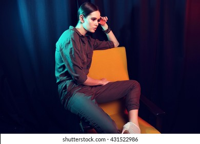 high fashion portrait of young elegant woman sitting in armchair.