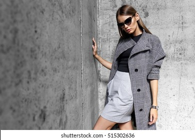 high fashion portrait of young elegant woman outdoor. Grey �oat, cat eye sunglasses, grey wall background