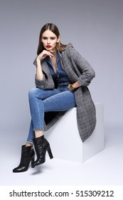 high fashion portrait of young elegant woman. Grey , skinny denim overall, black ankle boots