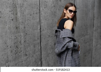 high fashion portrait of young elegant woman outdoor. Grey cat, cat eye sunglasses, grey wall background