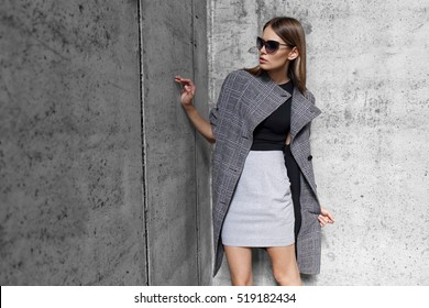 high fashion portrait of young elegant woman outdoor. Grey coat, cat eye sunglasses, grey wall background