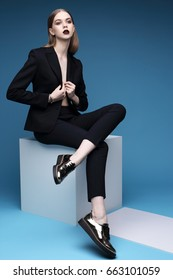 High fashion portrait of young elegant woman in black suit and loafers. Studio shot.