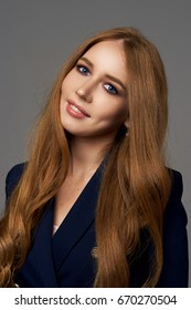High fashion portrait of young elegant woman wearing blue suit, standing and posing on gray background. Studio shoot. Pretty girl with long wavy hair.