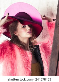 High fashion portrait of young woman in pink hat and fur coat at the white wall with wooden ladder